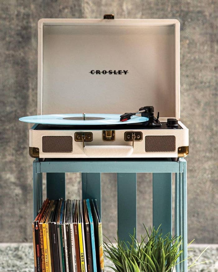 A record player on a small shelf with vinyls stacked below