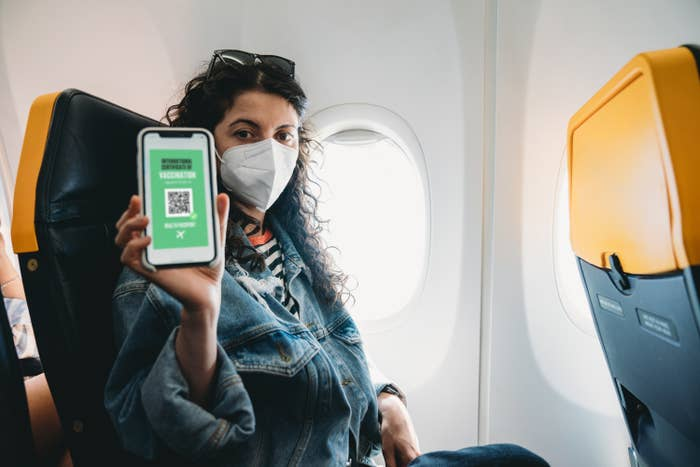 A masked airline passenger displaying her digital passport on her cellphone