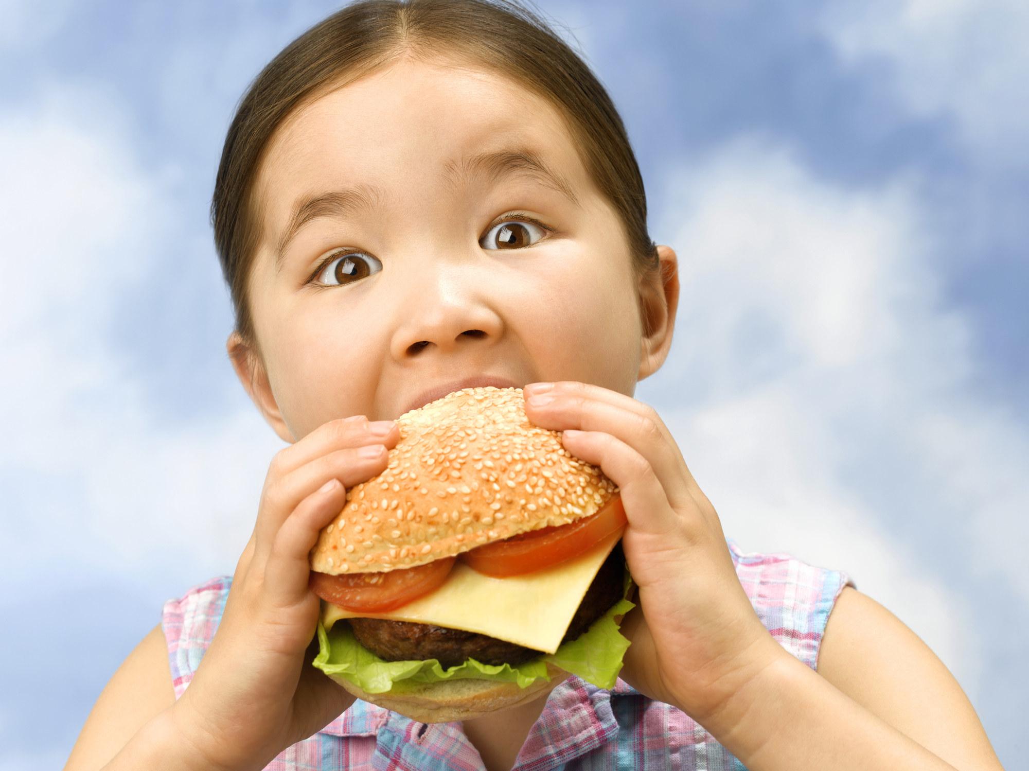 Little girl taking a bit of a big burger