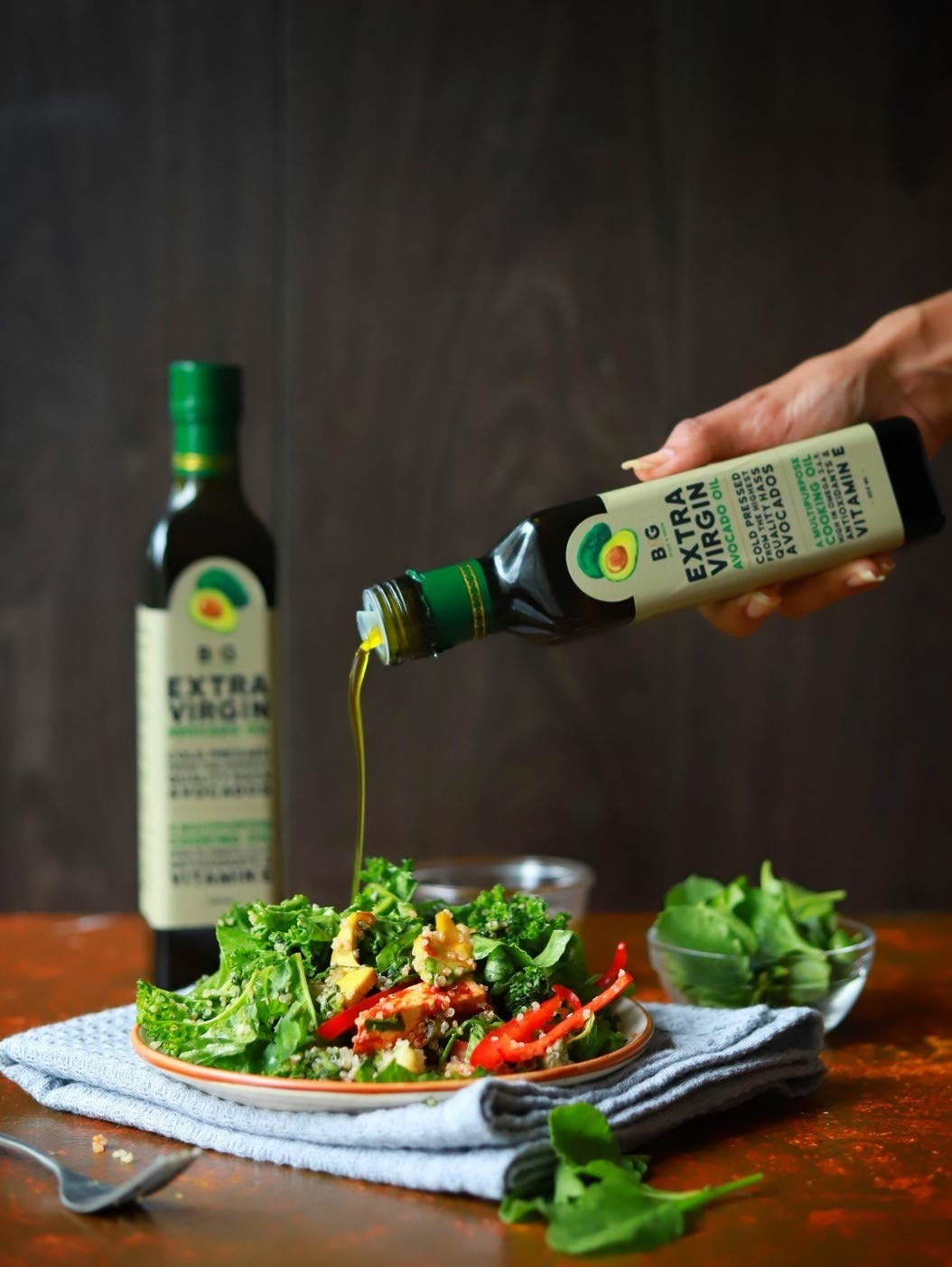 A person drizzling avocado oil on a salad