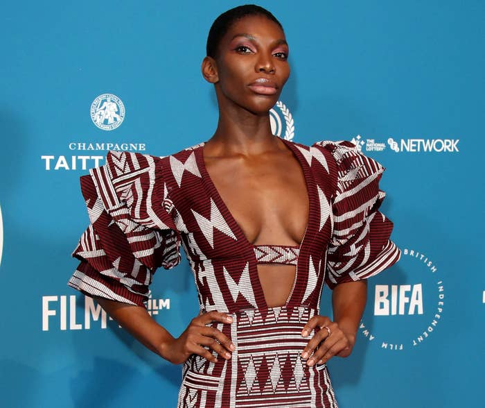 Michaela wears a maroon and while geometric patterned dress with a plunging neckline and layered sleeves