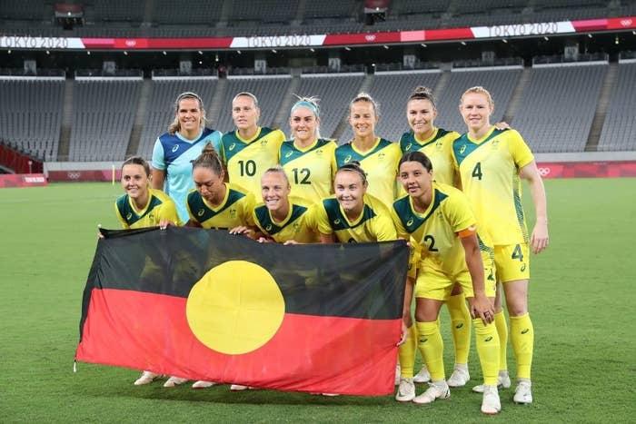The Matildas pose for a team photo with the Aboriginal flag prior to their match