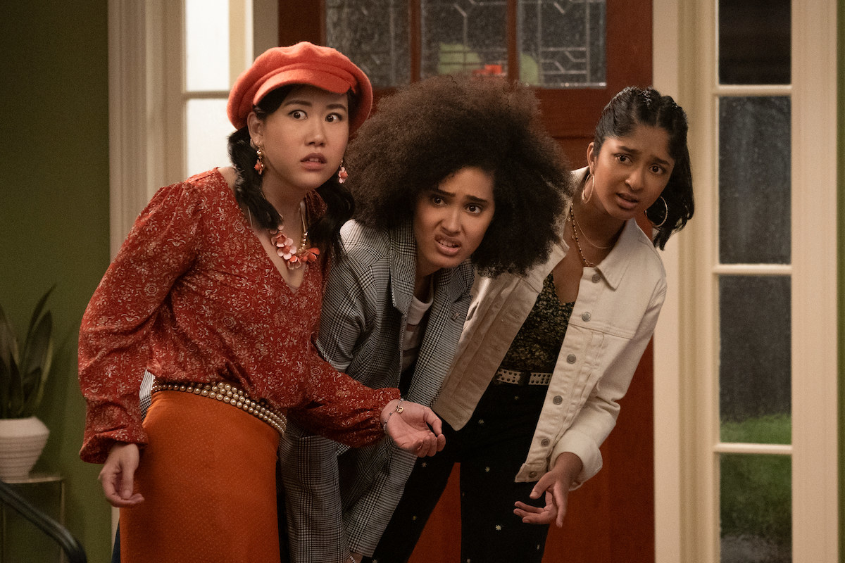Eleanor, Fabiola, and Devi peaking their head into the living room to spy