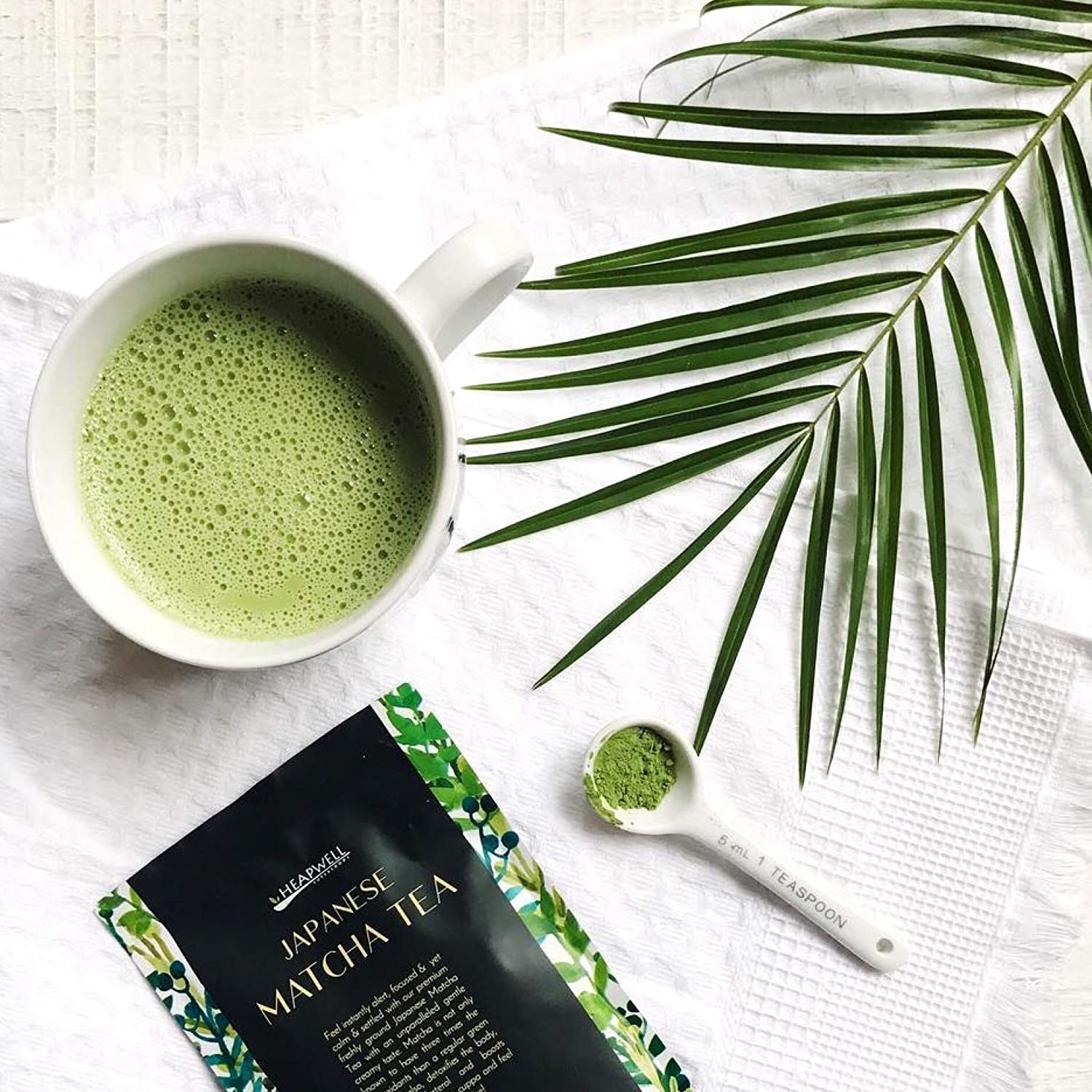 A mug of matcha pictured with a fern and the matcha packet