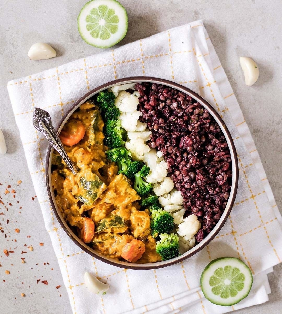 A one bowl meal consisting of black rice, cauliflower, broccoli, and curry