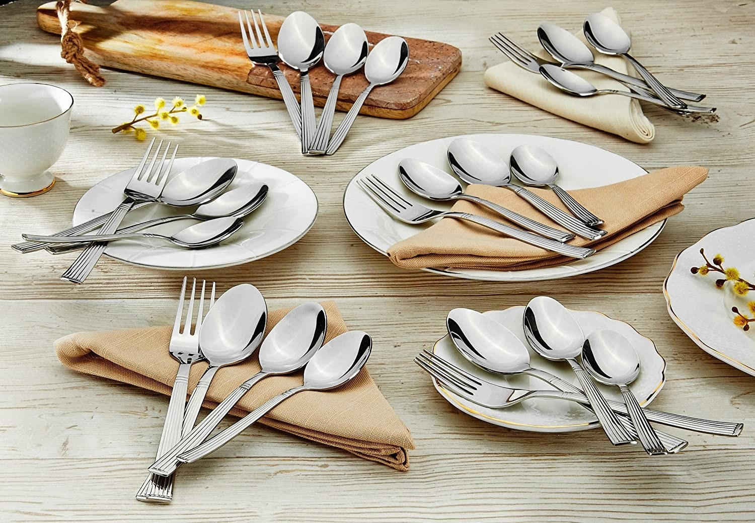 Sets of cutlery with forks, table spoons, tea spoons and dessert spoons on napkins and plates on a wooden table