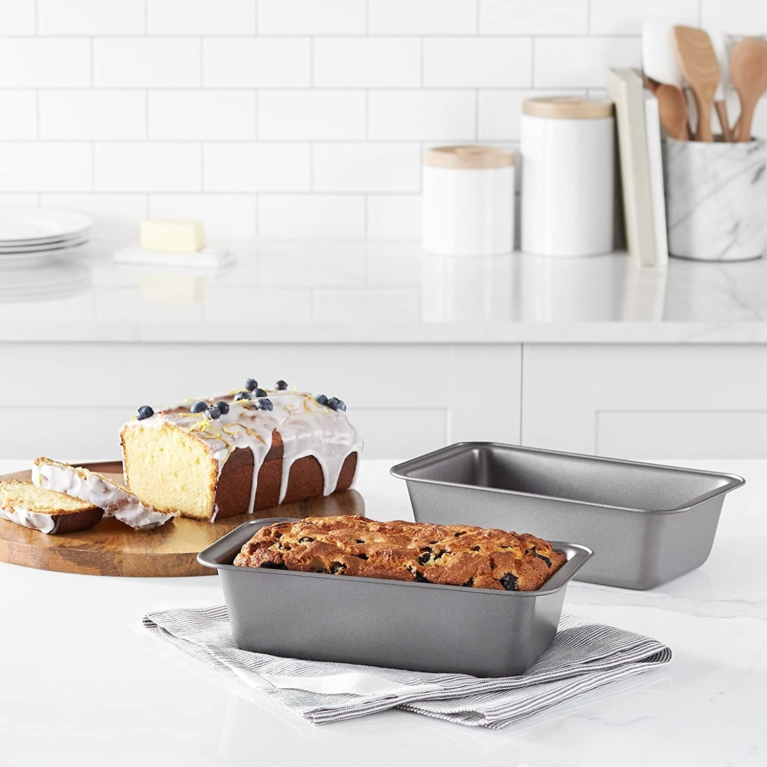 A set of baking trays with cakes in them next to a cake kept on a wooden board