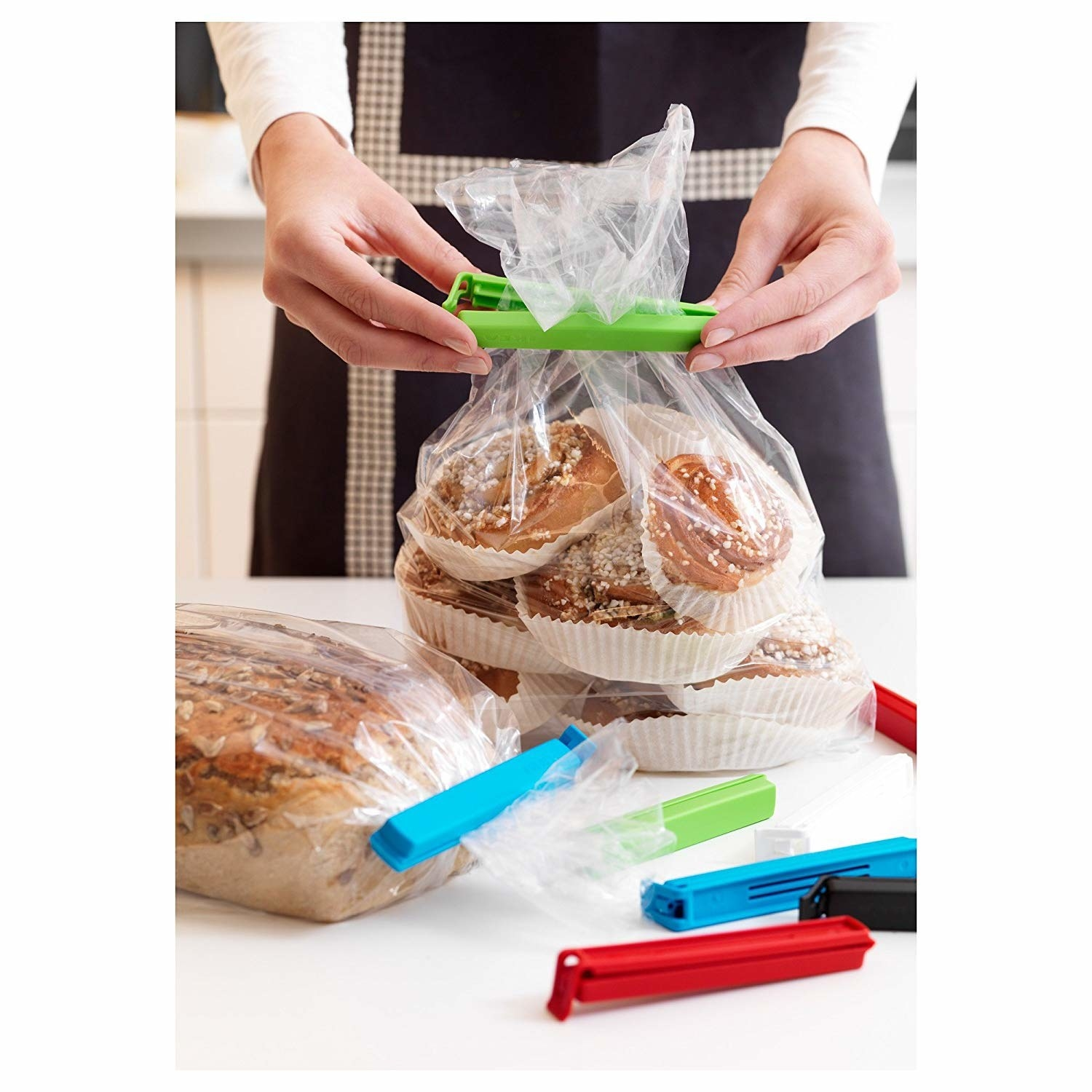 A set of bag sealing clips on a table next to a person closing a bag of bread rolls with the clips