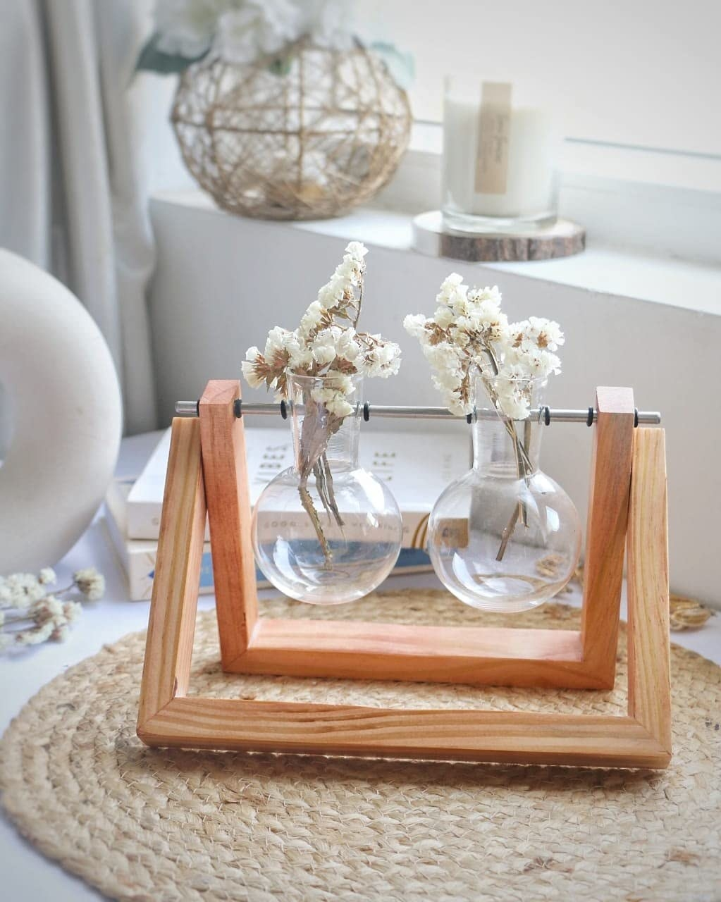A wooden two-legged table stand with two glass round bottom flasks with some white flowers in them