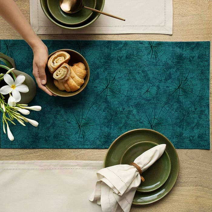 A teal blue suede table runner with green ceramic plates, a napkin, a bowl with baked items and a flower vase