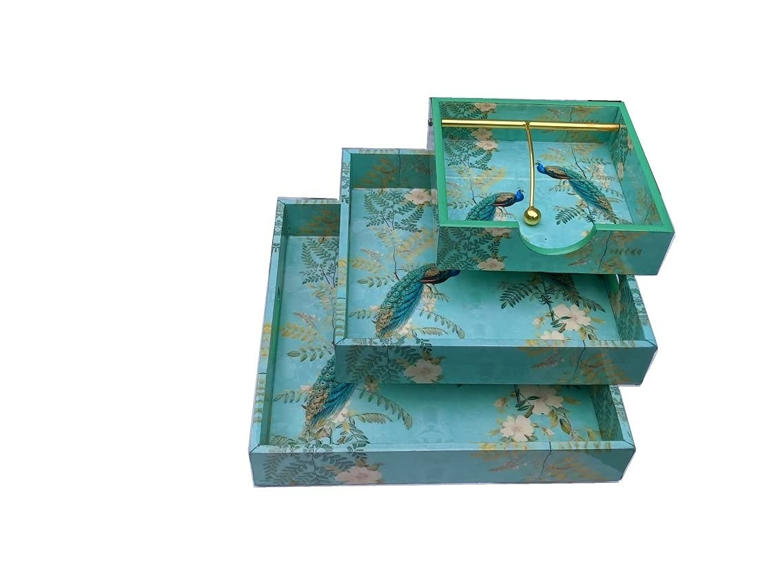 One blue printed napkin holder, two square printed blue trays with peacocks on the design stacked one on top of another