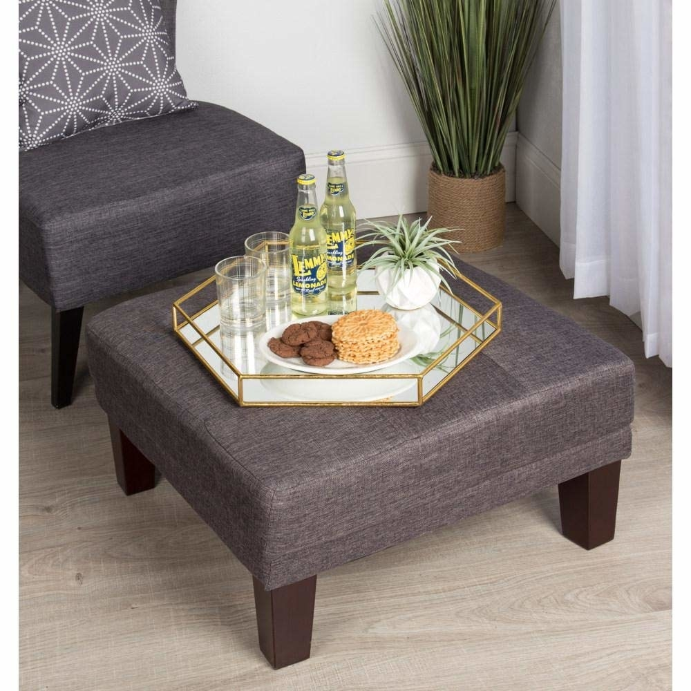 The hexagonal mirror tray placed on a grey settee with some crackers, empty glasses, two bottles of lemonade and a small indoor plant