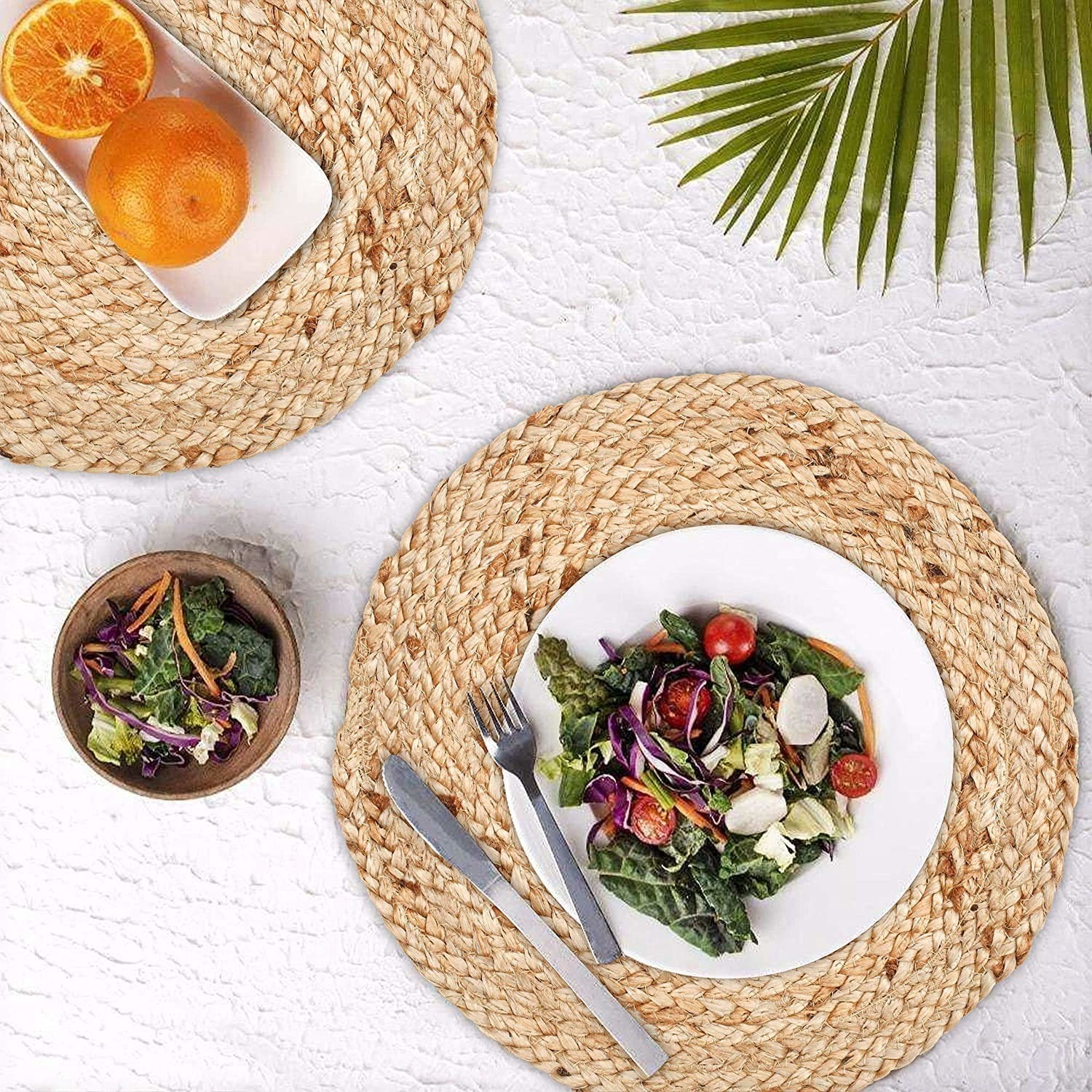 The round jute mats with two plates of food containing salad, a fork and knife and some oranges on another plate placed on a white background