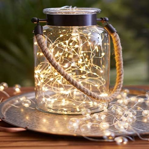 A glass jar with a jute handle and some fairy lights filled inside it