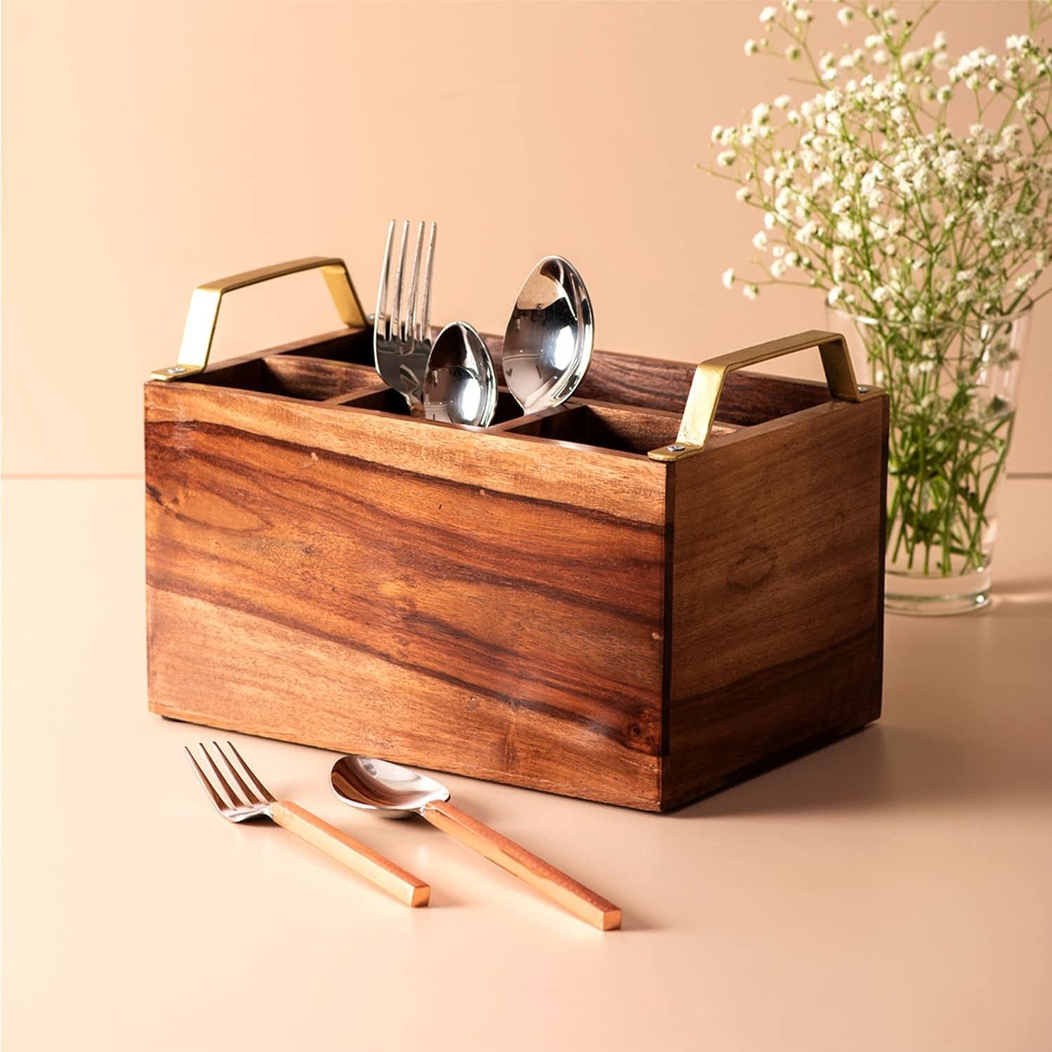 A wooden 4 compartment cutlery stand with some spoons in the holder, a fork and spoon in the foreground and baby's breath flowers in a vase