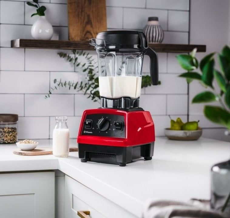 The Vitamix on a counter next to milk