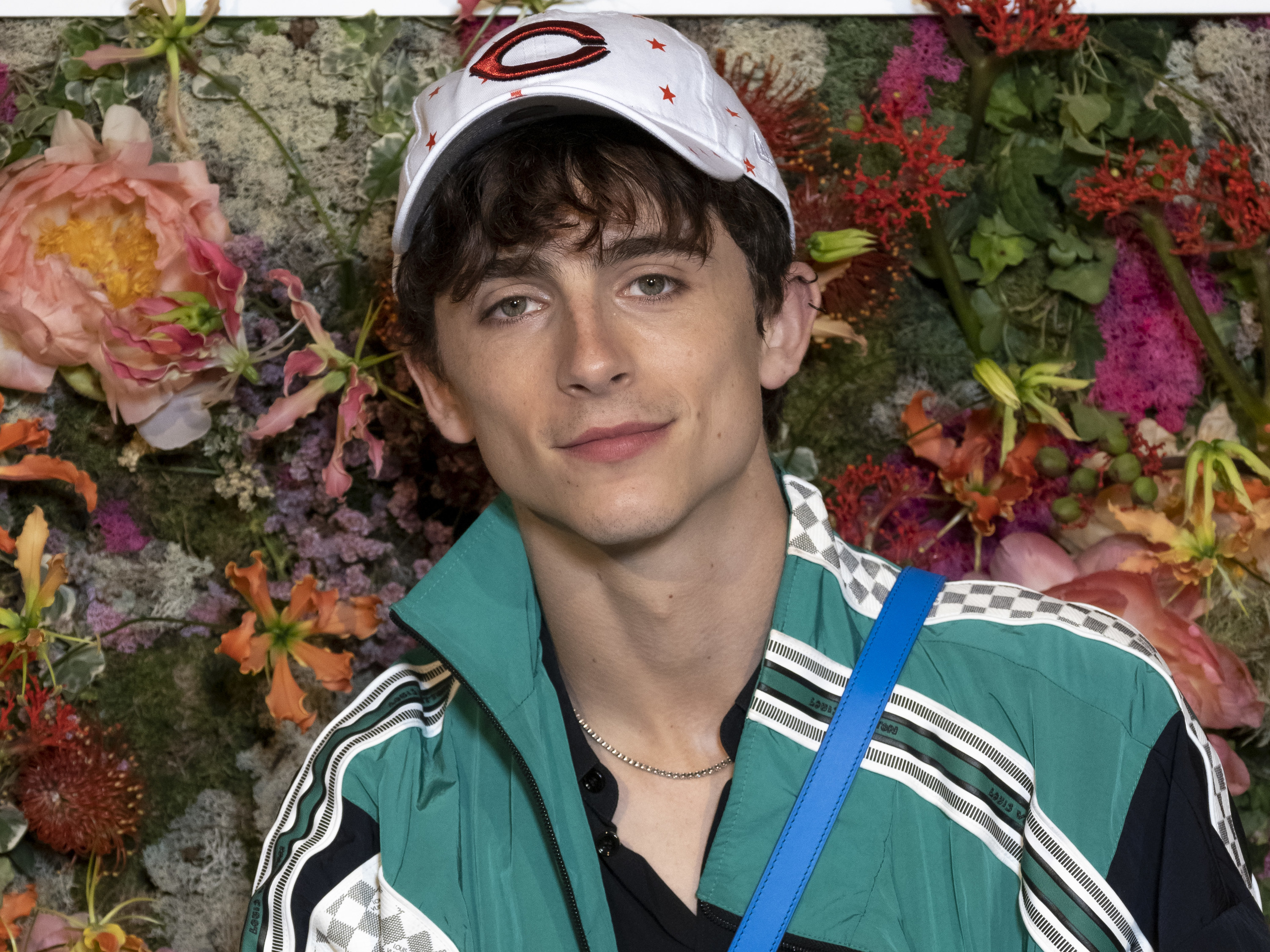 Timothée Chalamet is pictured standing in front of a floral backdrop at the Cannes Film Festival