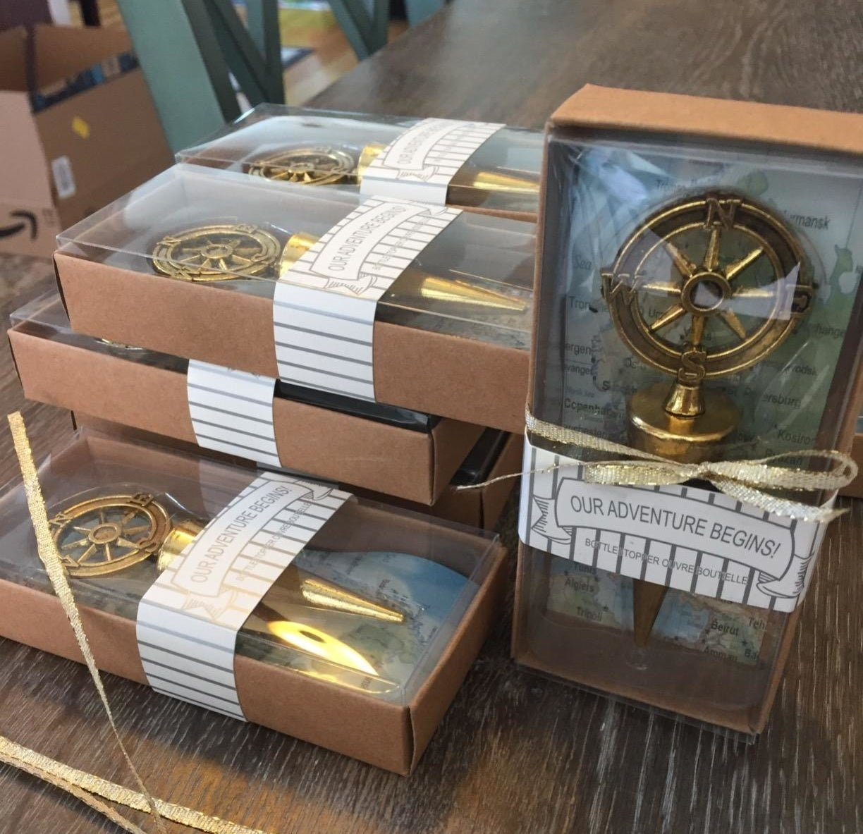 """Reviewer photo of a compass bottle stopper in gold in a box that says """"Our Adventure Begins"""""""