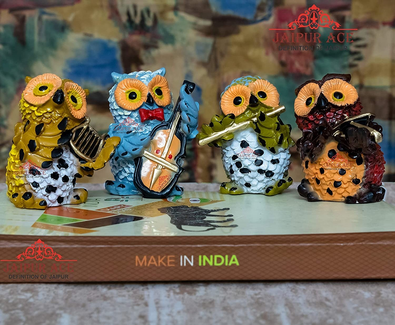 A set of 4 colourful owl showpieces holding musical instruments
