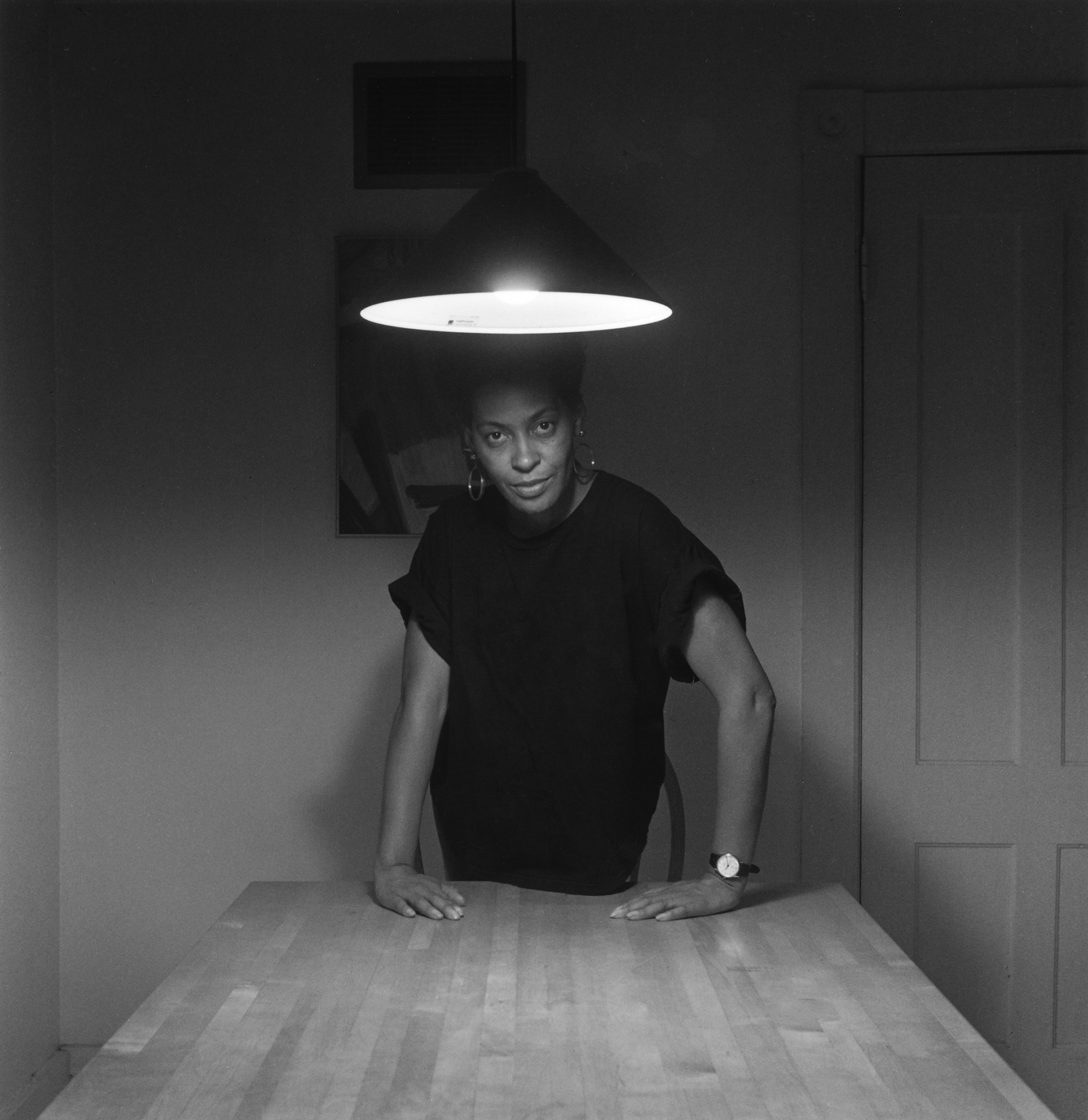 A woman stands under a kitchen light, facing the camera directly