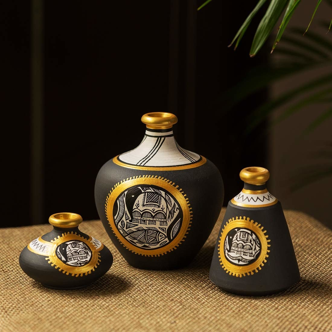 A set of 3 terracotta vases in black and gold of different sizes with Madhubani paintings on them
