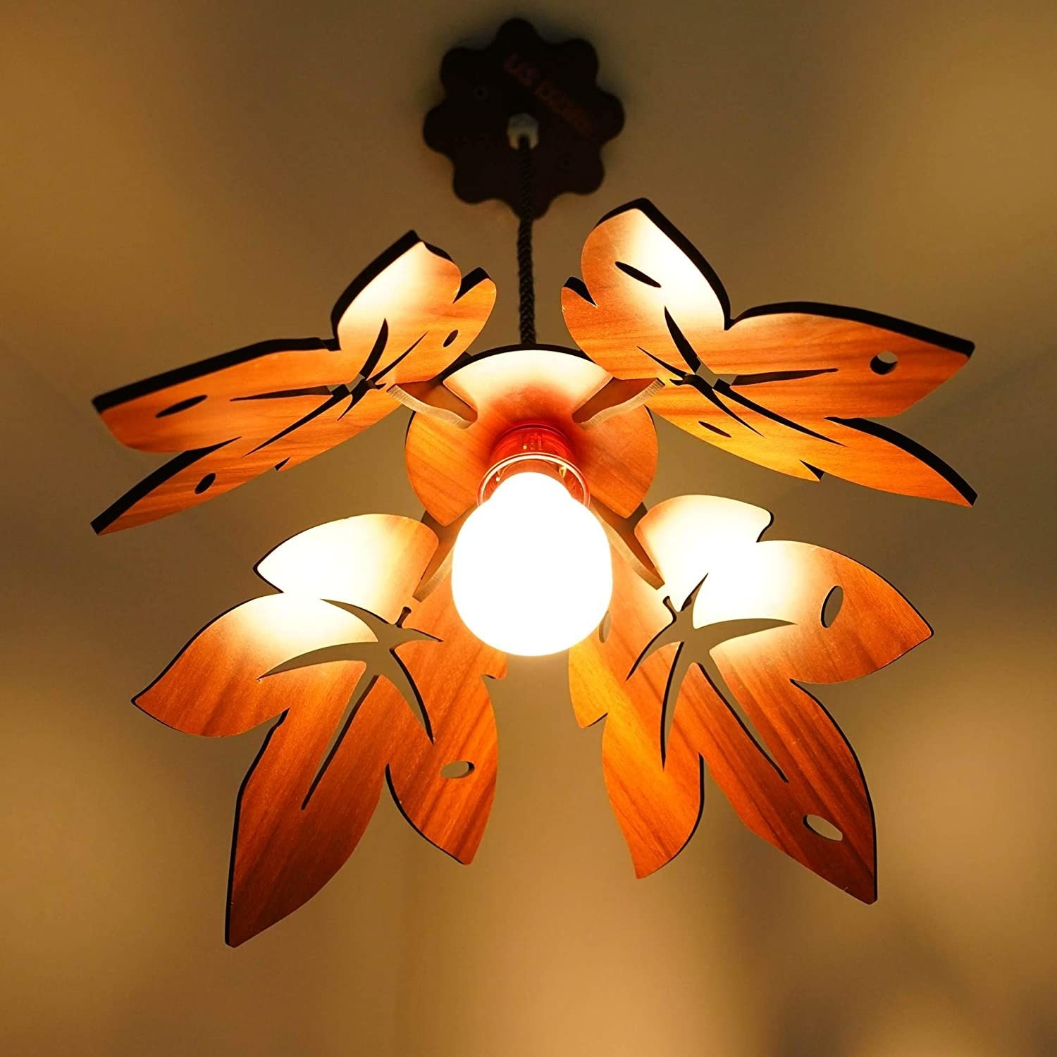 A lit hanging lamp with a wooden lampshade carved into leaves