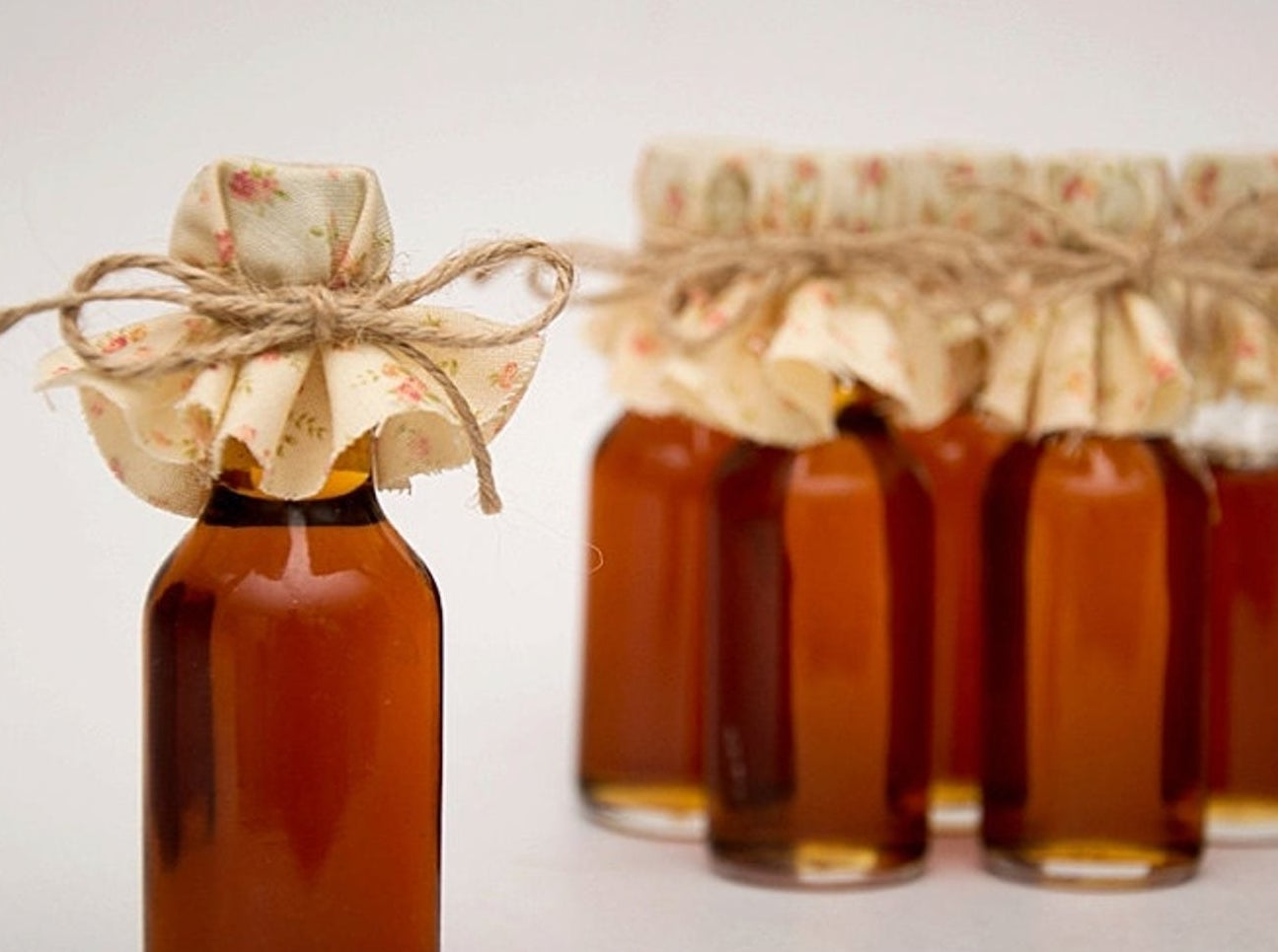 A close up of a bottle of maple syrup with a piece of fabric on the lid tied with twine
