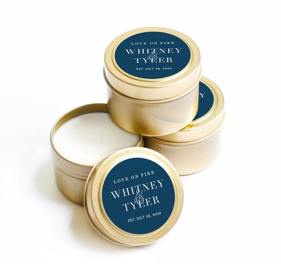 """Three white candles in gold tins with a blue label that says """"Love on fire, Whitney and Tyler, Established July 25, 2020"""""""