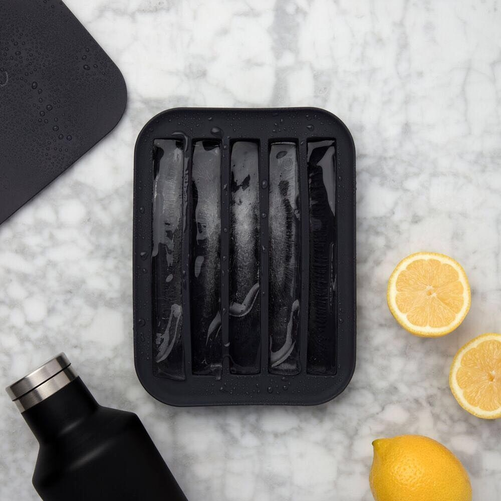 A flatlay of the ice tray filled with extra-long ice sticks, surrounded by fresh lemons