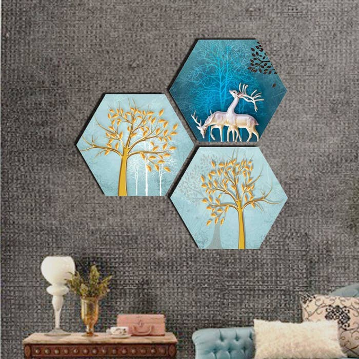 A set of 3 textured hexagonal paintings of a reindeer and two trees in gold with a blue background colour