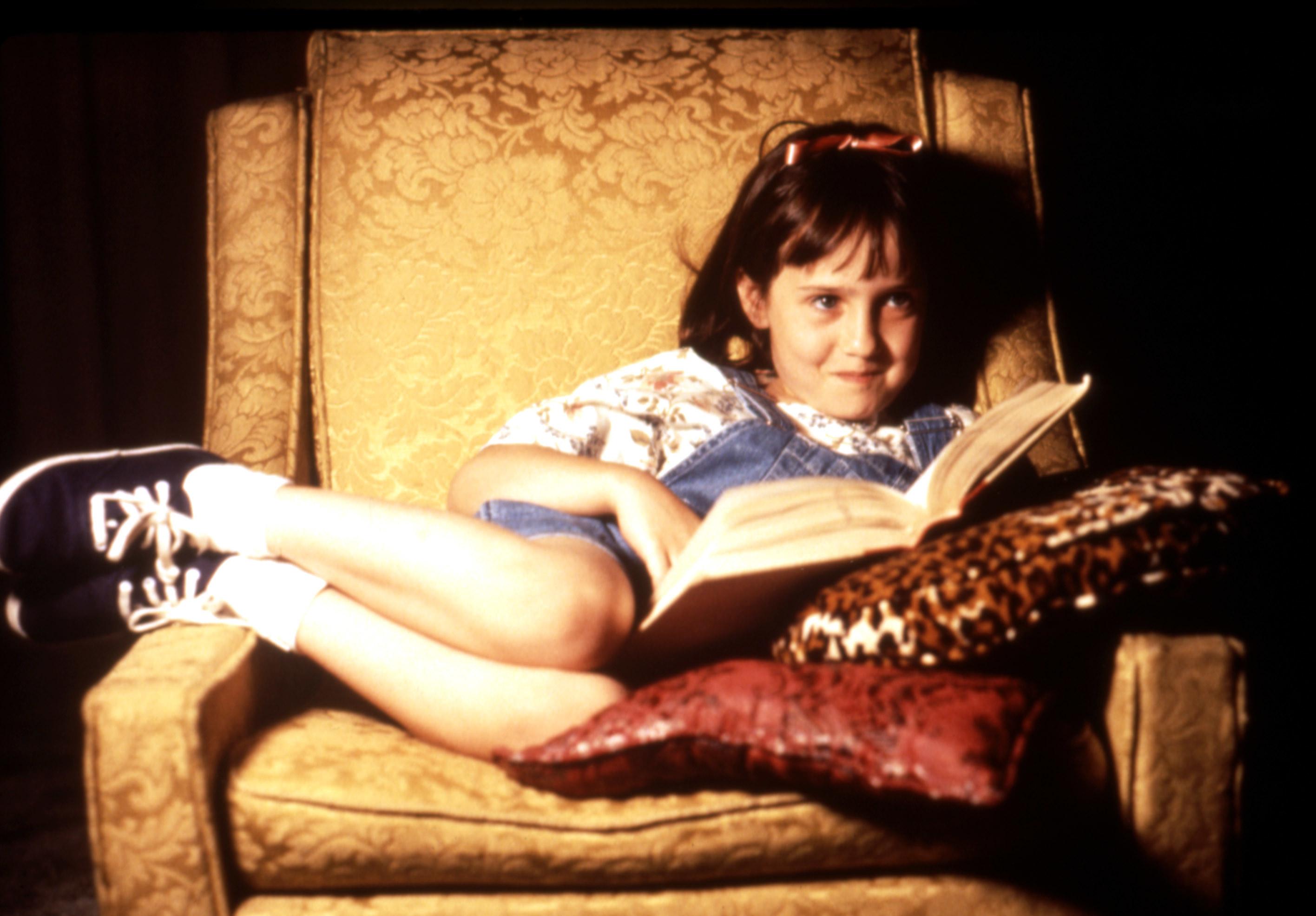 Mara Wilson as Matilda, reading in a chair