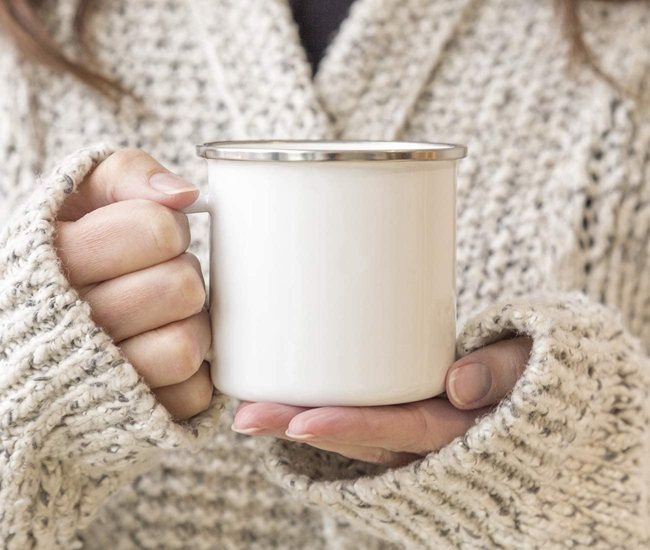 Model is holding a blank white campfire mug with a stainless steel rim