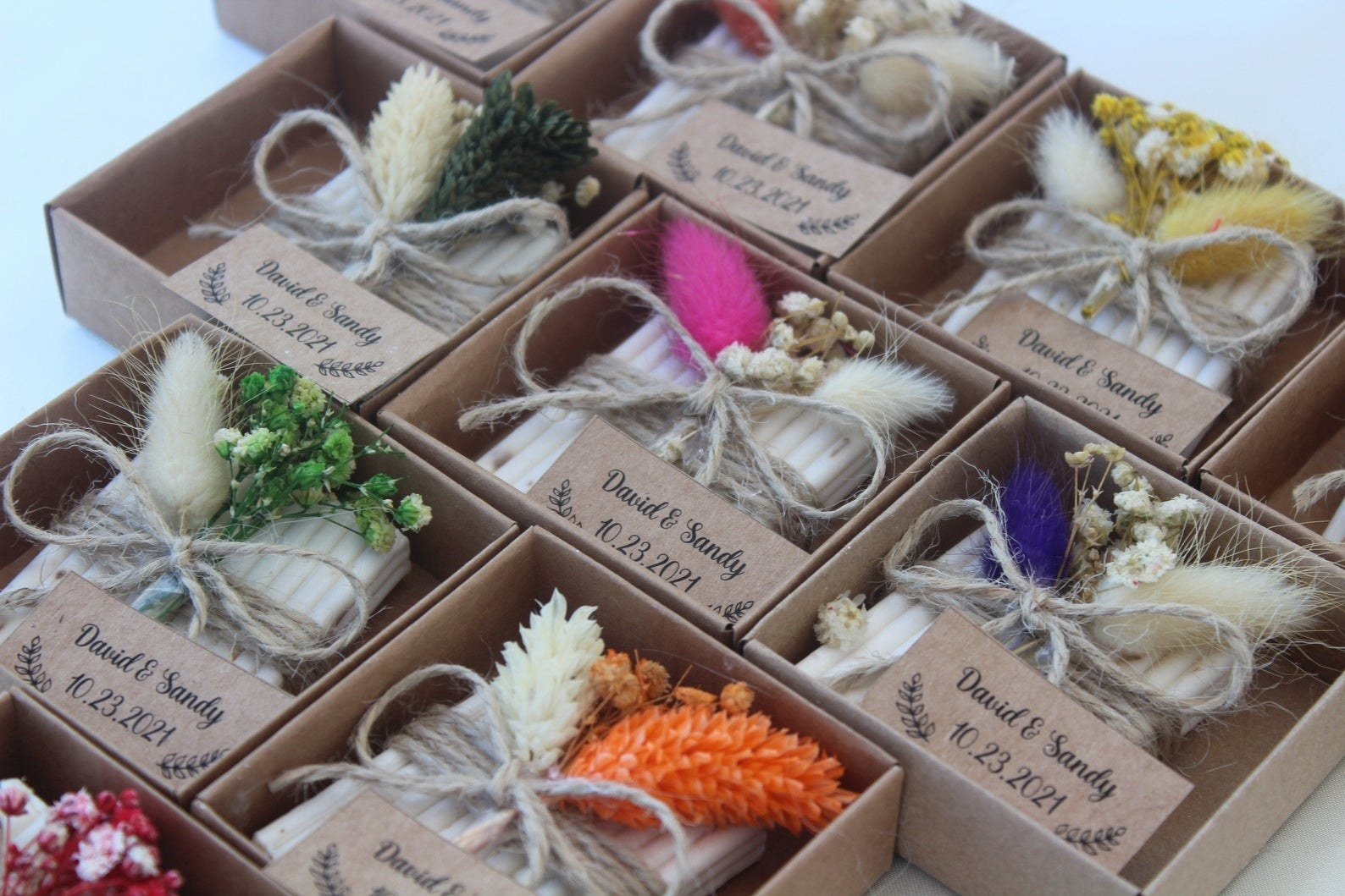 """Eight bars of soaps wrapped with twine, flowers, and a personalized tag that says """"David and Sandy"""" with a date"""