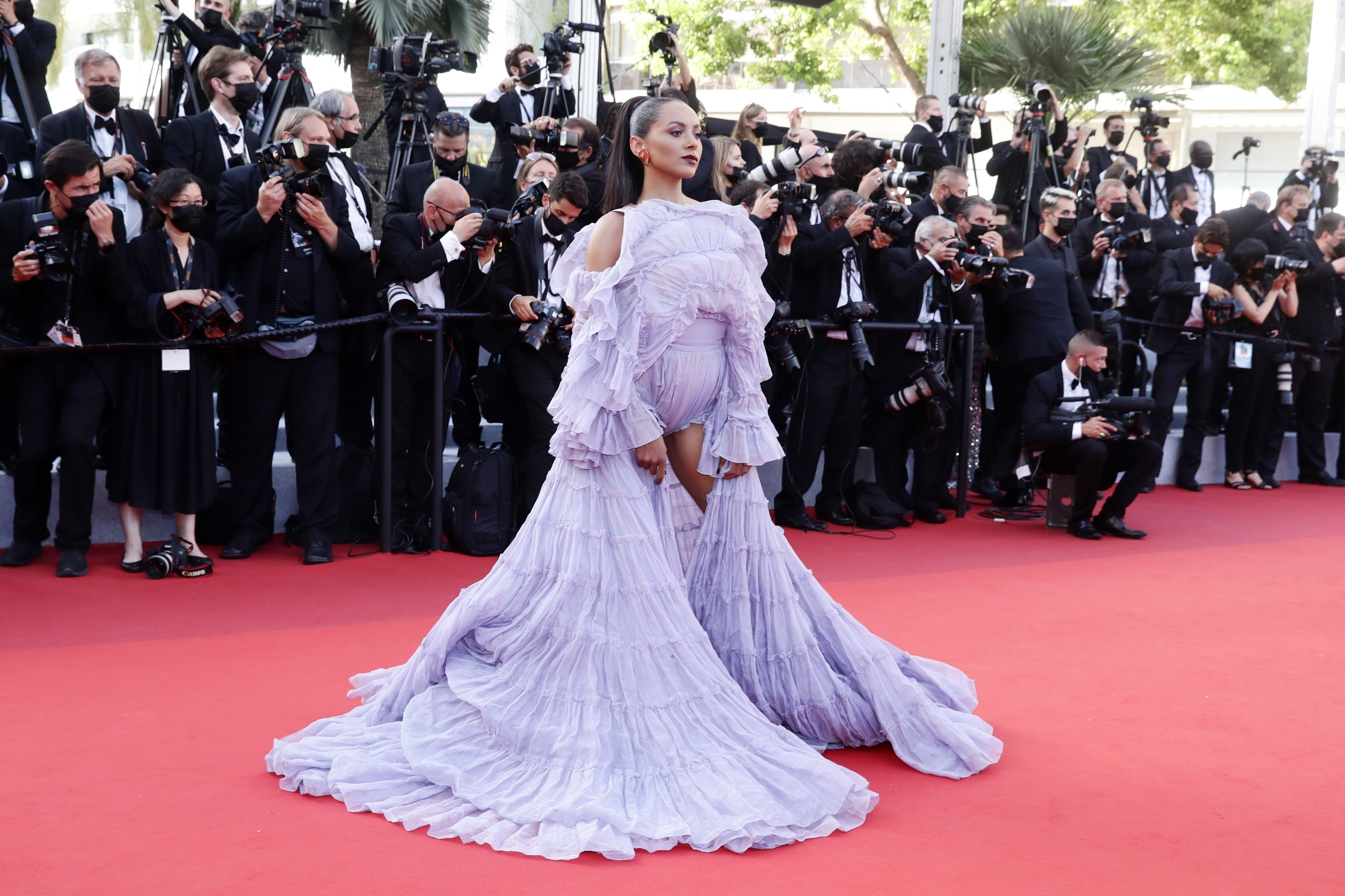 A woman stands in a very frilly purple dress at Cannes