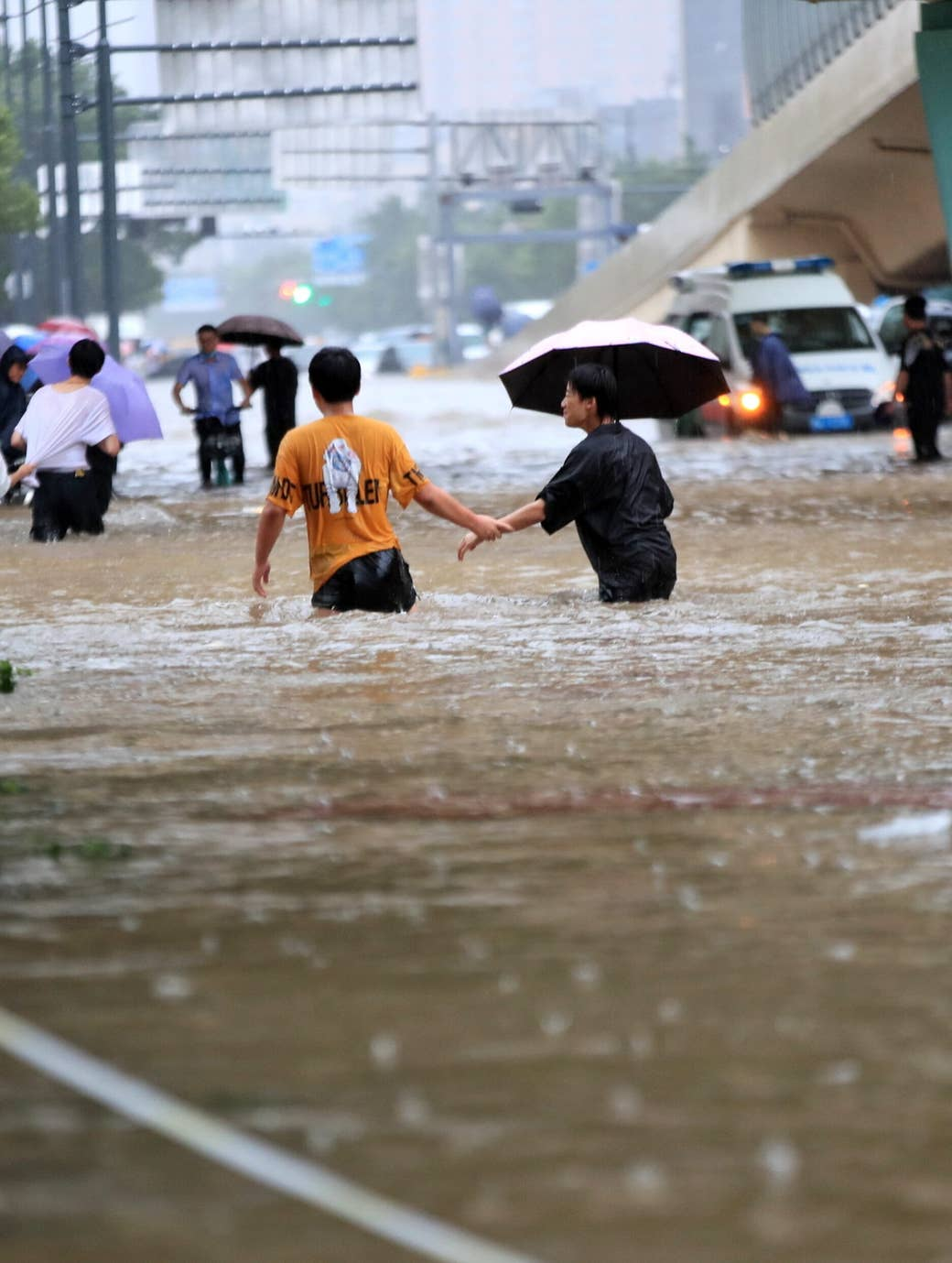 People in China walk through waist-high water due to recent flooding, one carries an umbrella