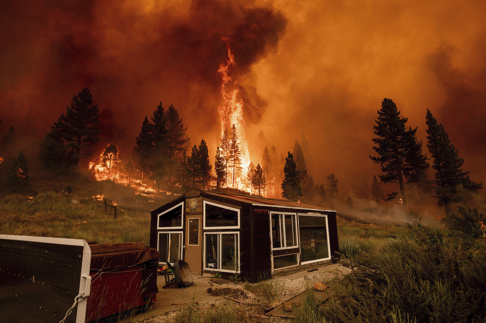 A small structure in the foreground as a hilly forest is engulfed in flames behind it