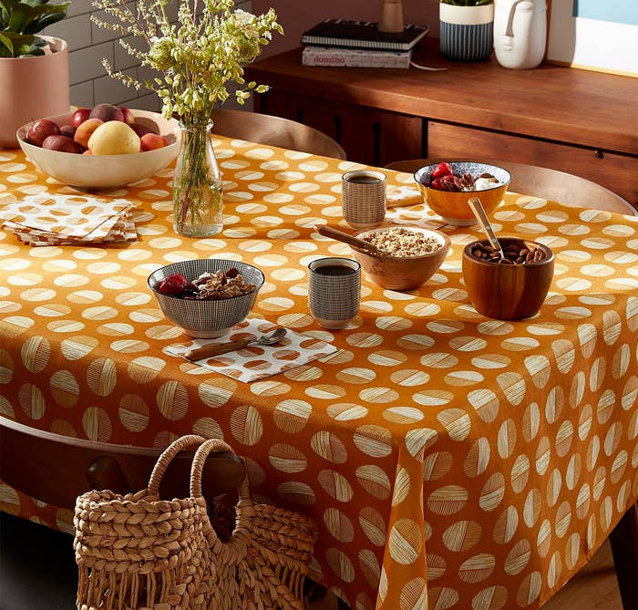 a circle-patterned table cloth on a table with dinnerware on top