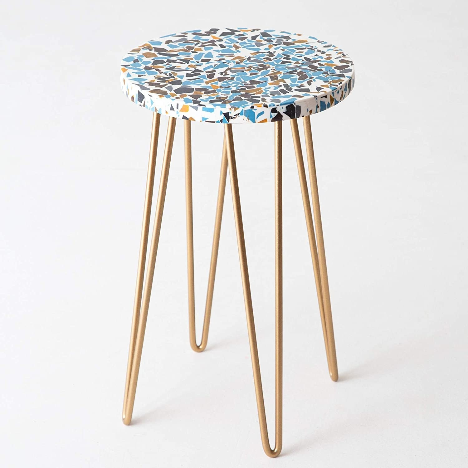 A resin stool with golden hairpin legs and an abstract print on the table top