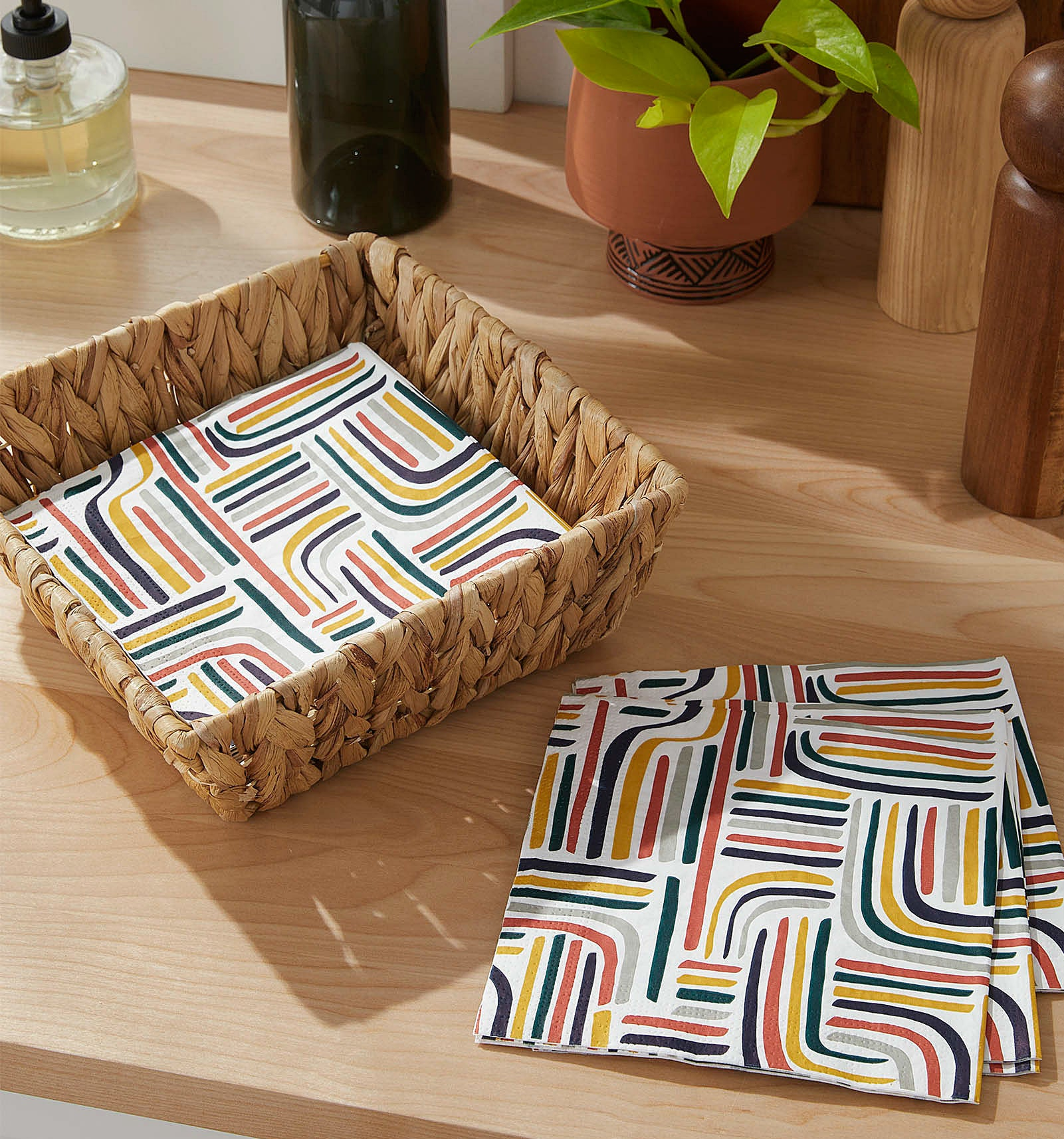 Vibrant paper napkins in and beside a cute basket on a counter