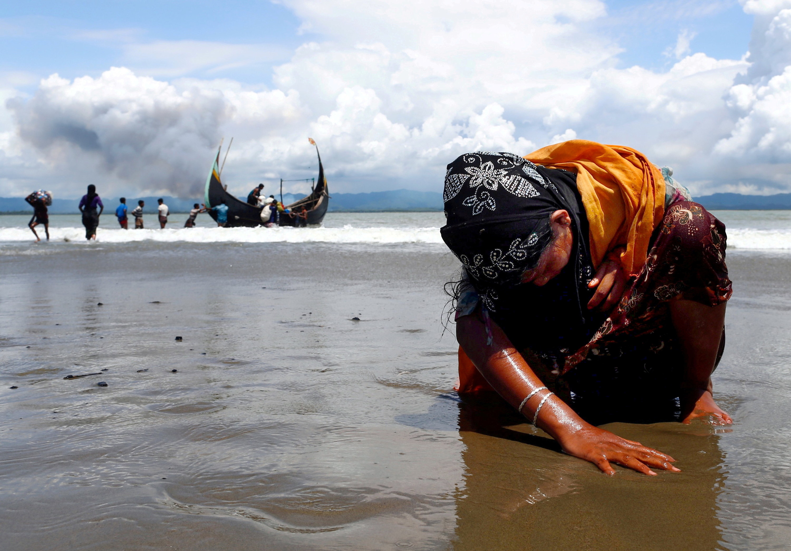 A woman leans down and places her hands on the sand, a boat with people is in the background at the beach behind her