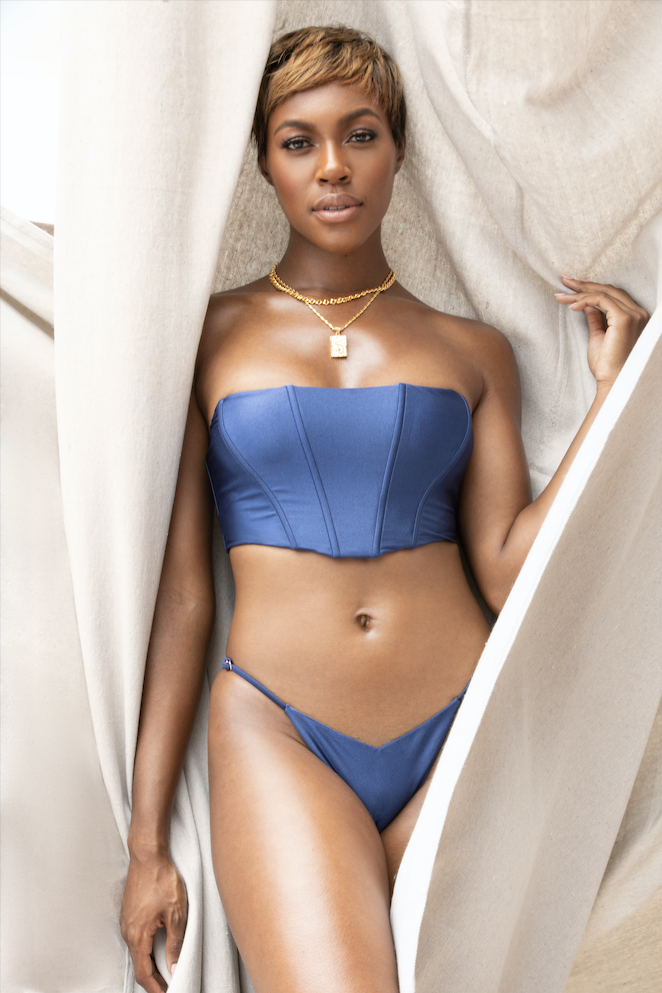 a model wearing the navy siren corset top and matching thong
