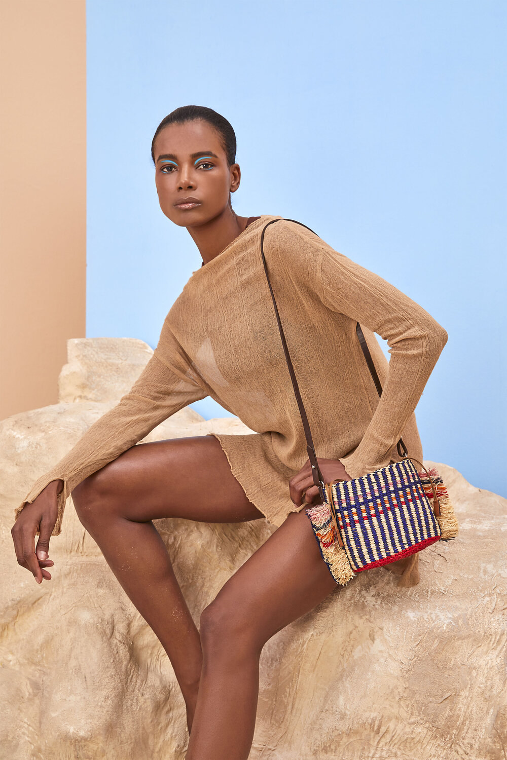Model wearing the light tan woven bag with navy stripes and ruffles down the side