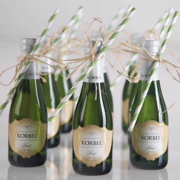 Korbel mini champagne bottles with straws and ribbon tied to it