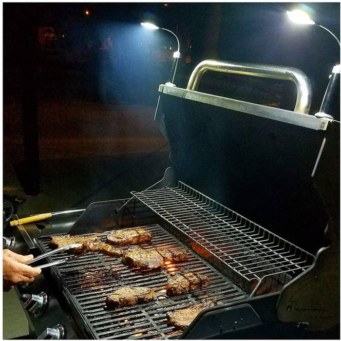Model grilling meat on a barbecue at night while using the lights, magnetically attached to the grill