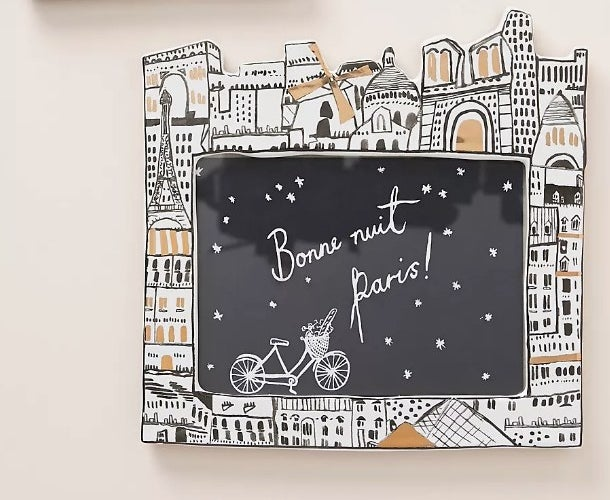 A picture frame with a black/white/gold cityscape frame