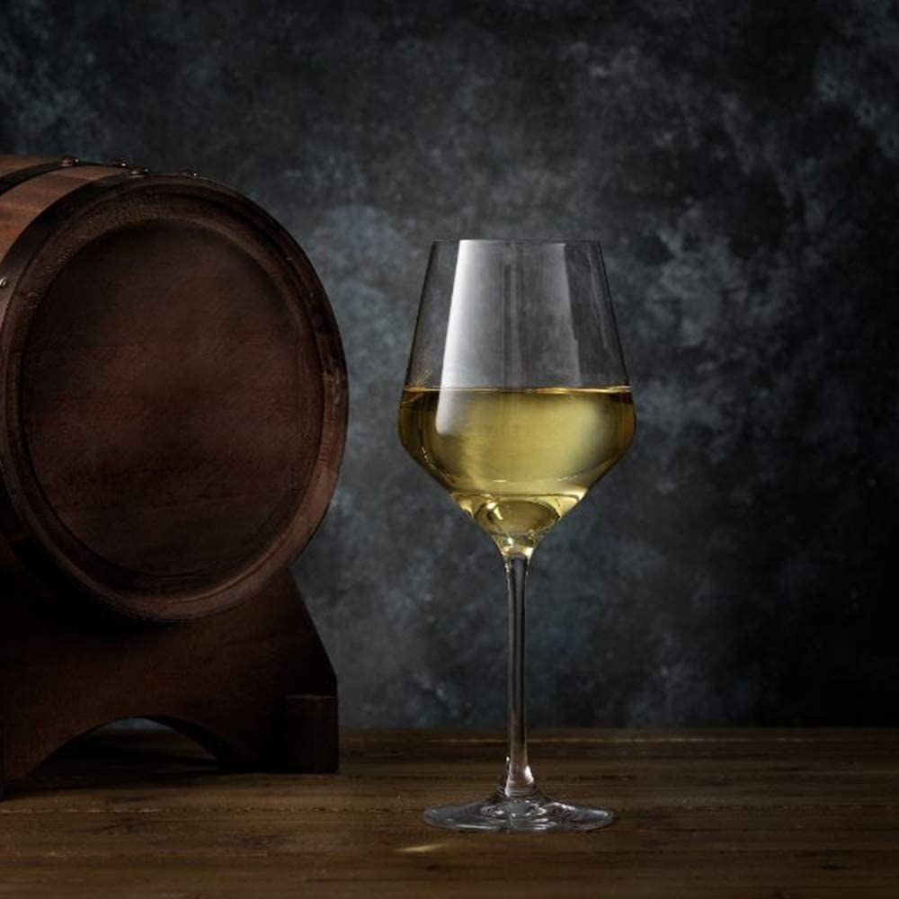a glass of wine next to a barrel on a table
