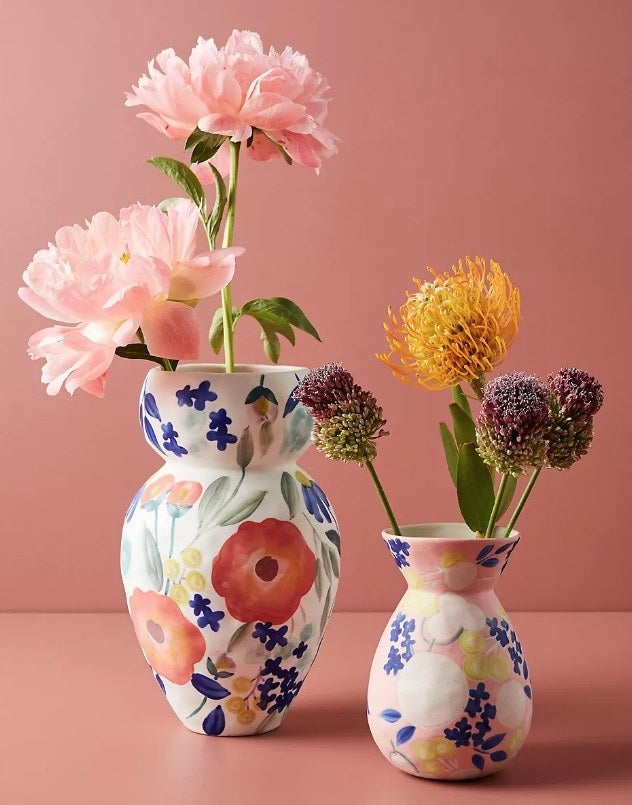 Two handcrafted stoneware vases; one larger in white and one smaller in pink, both painted with floral designs and filled with flowers