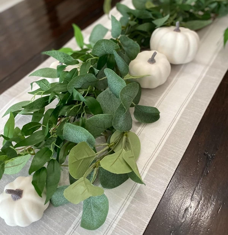 Reviewer photo of white pumpkins next to a green garland
