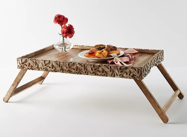 A brown, wooden, rustic-style breakfast tray with folding legs