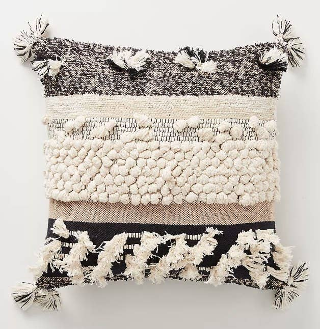 A black/beige/cream, boho-style throw pillow with textured details